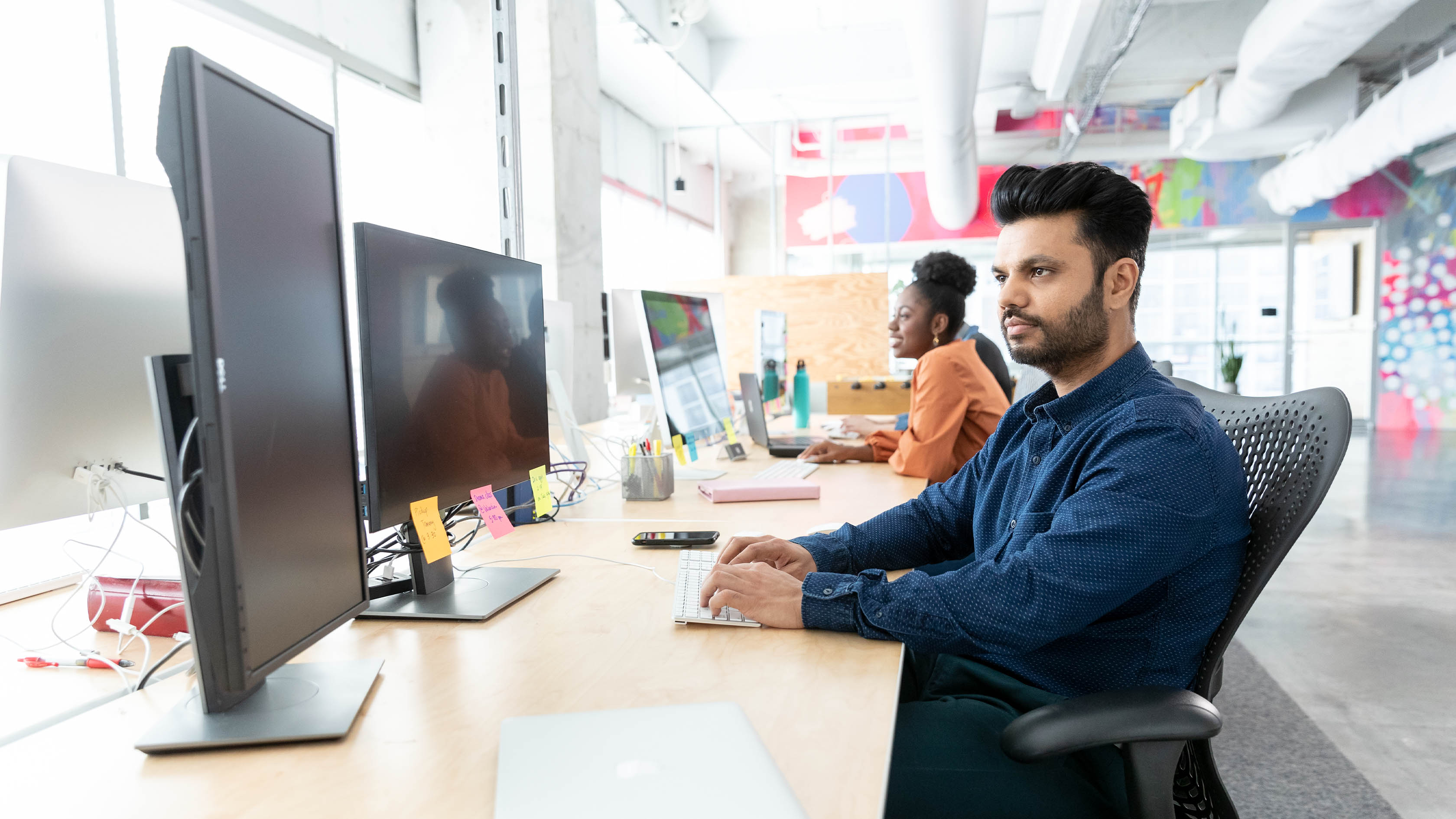 Workers looking at computers in bright office space