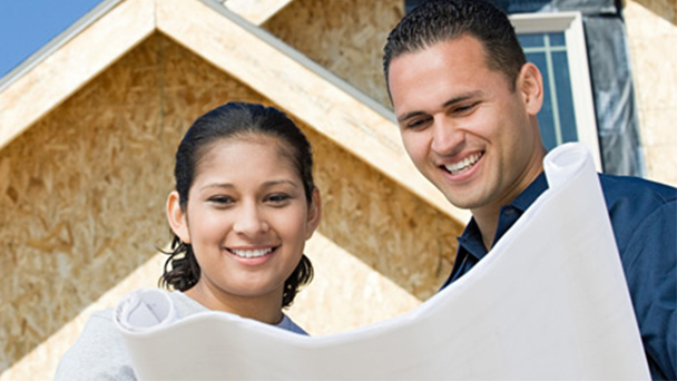 Man and woman looking at blueprints in front of house under construction