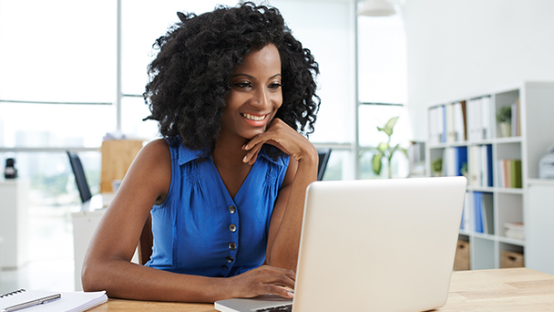 Woman working at laptop in open office