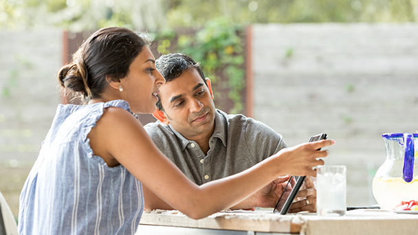 Couple looking at iPad together outside