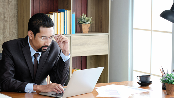 Adult professional businessman wearing glasses and black suit sitting for working within a modern office. Handsome bearded man using a laptop on the workplace.