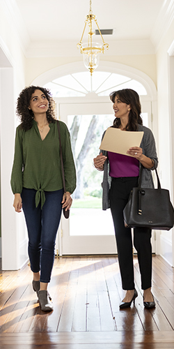 Realtor showing young woman around a home.